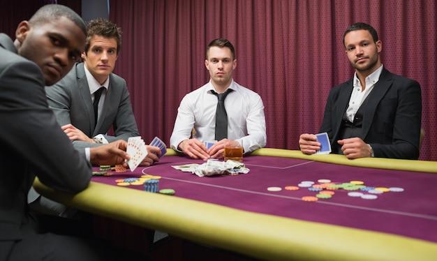 Homens que olham para cima do jogo de poker de altas apostas