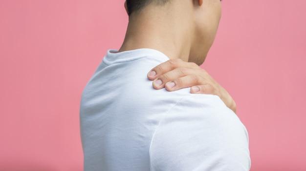 Homens que sentem a dor em seu ombro em um fundo cor-de-rosa.