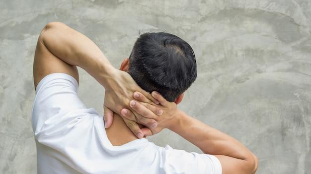 Homens que sentem a dor em seu pescoço em um fundo cinzento.