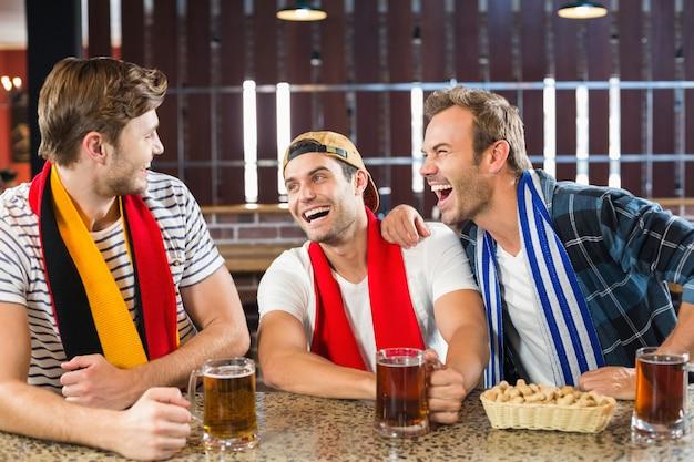 Homens rindo com cervejas nas mãos