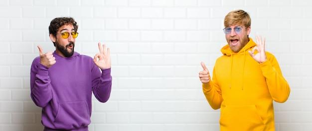 Homens se sentindo feliz, surpreso, satisfeito e surpreso, mostrando bem e polegares para cima gestos, sorrindo
