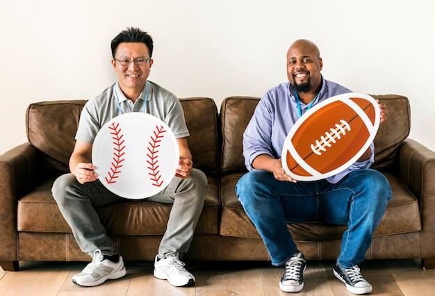 Homens, segurando, basebol, e, rugby, ícones, sentar sofá