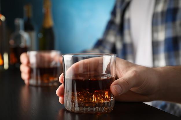 Homens segurando copos de uísque no bar, espaço para texto