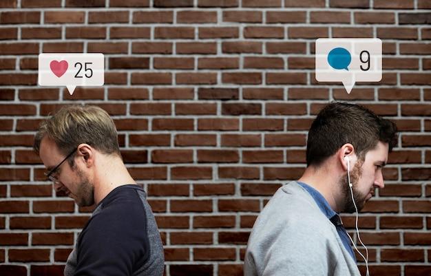 Homens sentados de costas um para o outro usando as redes sociais