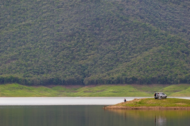 Homens sentados e pescando na ilha na barragem entre as montanhas.