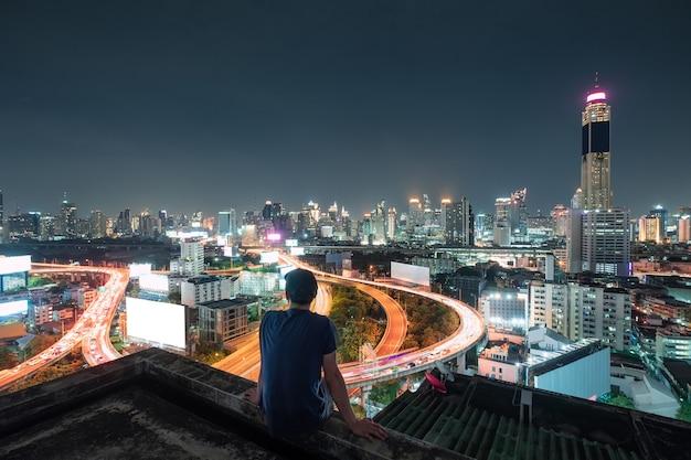 Homens sentados na varanda com vista para a cidade brilhando à noite