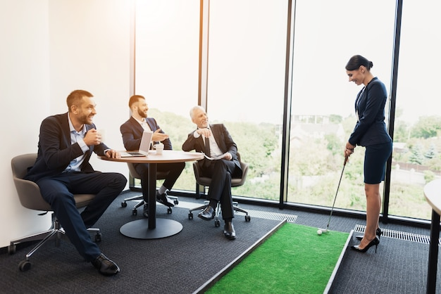 Homens sentam em uma mesa e assistem uma mulher em um terno de negócio