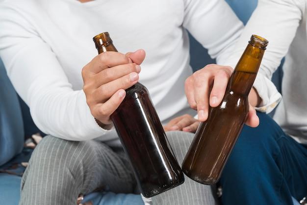 Homens, sentando, com, cerveja, ligado, sofá
