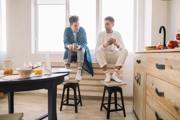 Homens, sentando, perto, janela, segurando, copo café