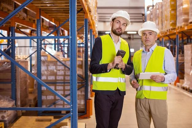 Homens simpáticos e sérios em pé no armazém enquanto trabalham juntos em equipe