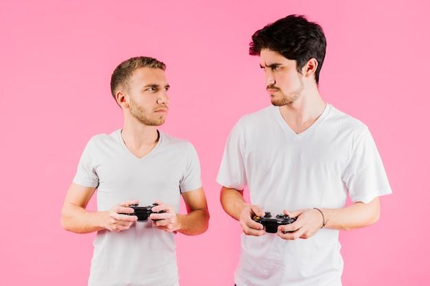 Homens sombrios com joysticks olhando uns para os outros