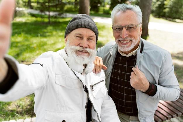 Homens sorridentes de tiro médio tirando selfies