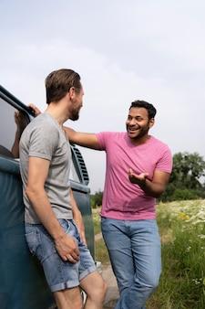 Homens sorridentes em tiro médio conversando perto da van