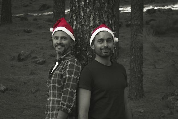 Homens sorridentes posando com chapéus vermelhos de natal perto do tronco de um pinheiro no parque florestal. casal gay feliz