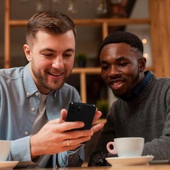Homens sorridentes usando smartphone em um café