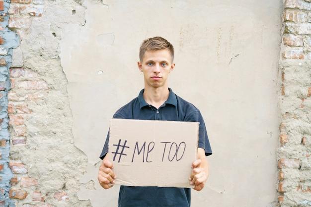 Homens sozinhos com expressão deprimida e mostrando um papel com um texto #metoo