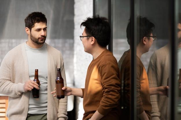Homens tiro médio com cervejas