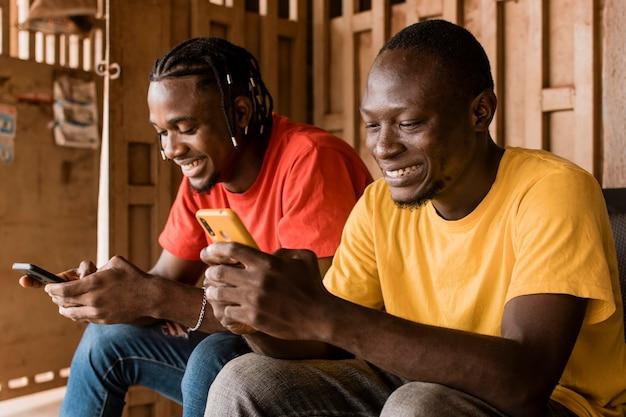 Homens tiro médio com smartphones