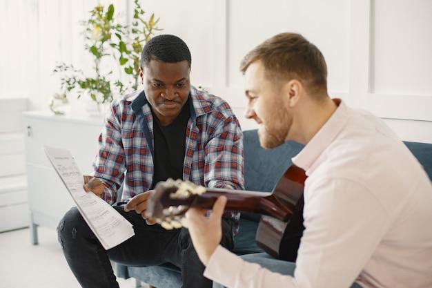 Homens tocam violão. escrever música. homens africanos e caucasianos.