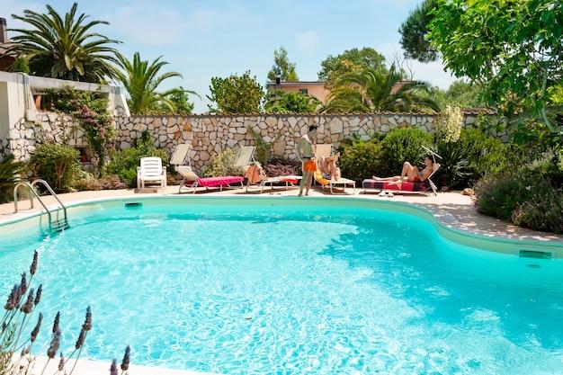 Homens tomando banho de sol ao lado da piscina