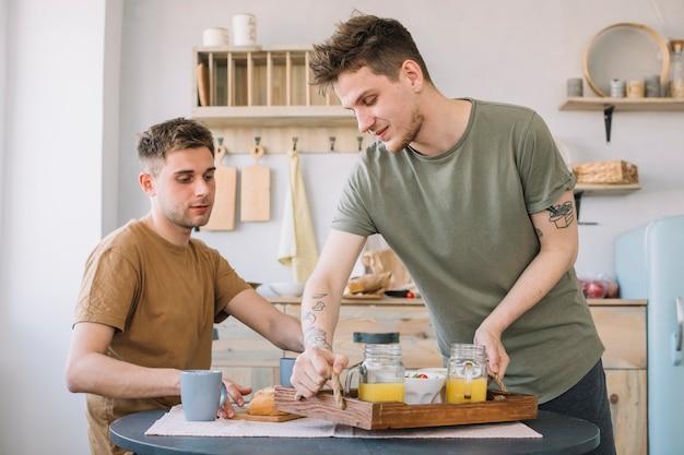 Homens tomando café da manhã na mesa de jantar na cozinha