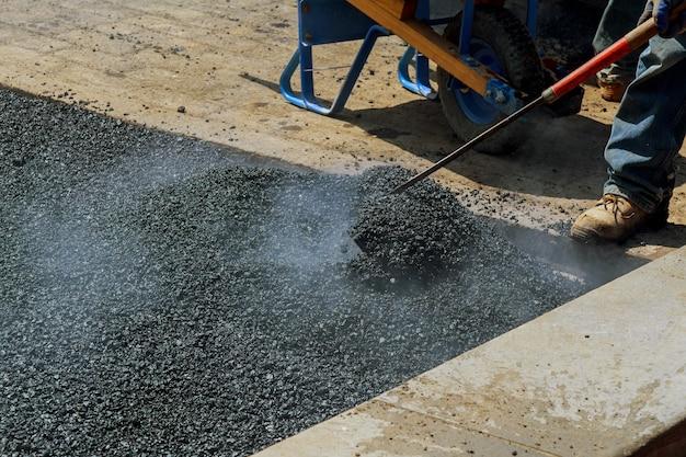Homens trabalhando duro na estrada de asfalto com pás
