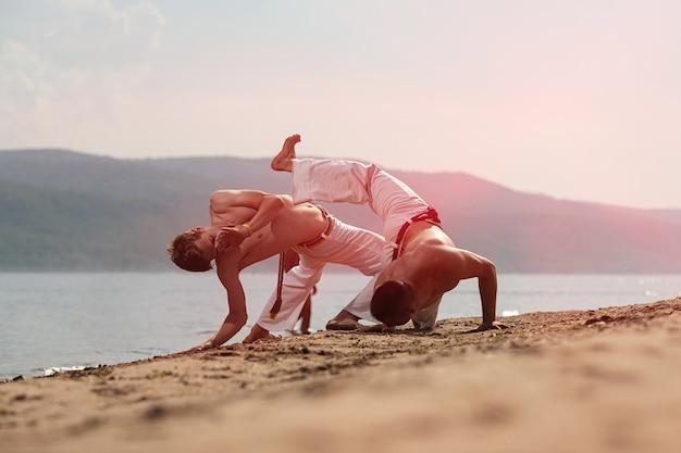 Homens treinam capoeira na praia