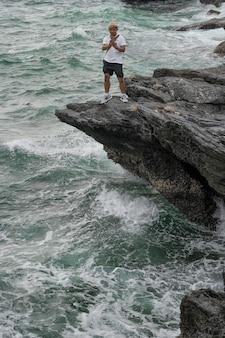 Homens, turistas estão tirando fotos do mar pelo celular.