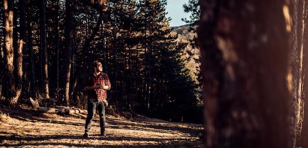 Homens usando telefone inteligente numa floresta de pinheiros e olhando para a distância