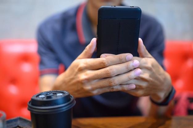Homens verificam e-mails com telefones celulares.