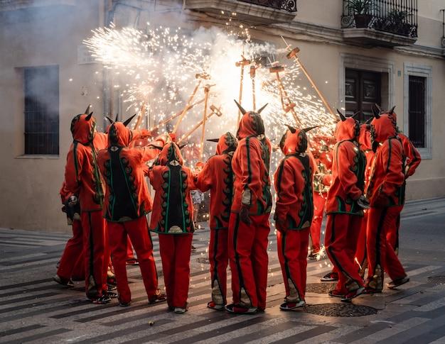 Homens vestidos como demônios brincando com fogos de artifício