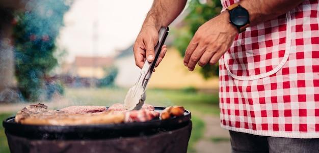 Homens vestindo avental assando carne de frango