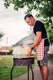 Homens vestindo avental de churrasco de carne no quintal