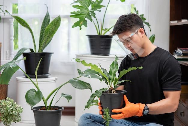 Homens vestindo luvas laranja e plantando árvores dentro de casa.