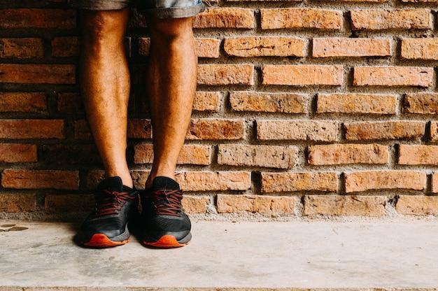 Homens vestindo sapatos pretos, em pé na frente do tijolo vermelho.