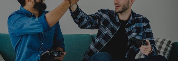 Homens, videogame jogo, ligado, sofá, dar, um ao outro, um, alto cinco, lazer, e, trabalho equipe, conceito