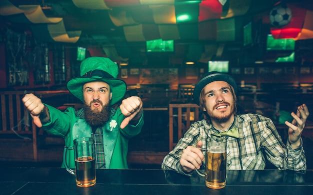 Homens ypung muito chateados mostram grandes polegares para baixo e olham para cima. eles se sentam no balcão do bar no pub. o cara da esquerda veste o traje de são patrício.