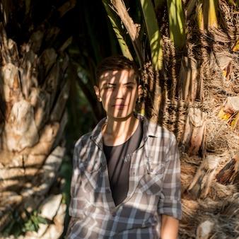 Homossexual em pé na sombra perto da árvore