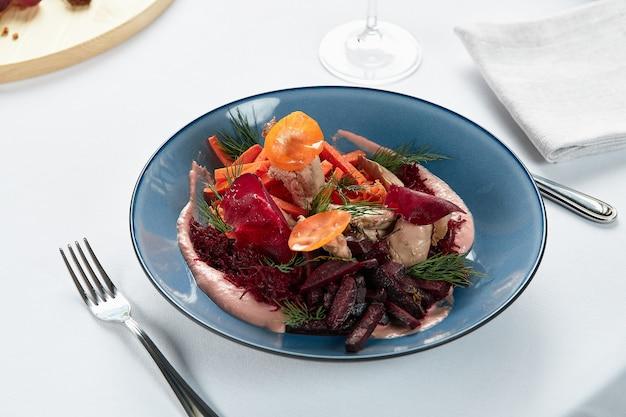 Homus com legumes, húmus de beterraba com palitos de legumes salteados e folhas de esbelta, fundo claro.