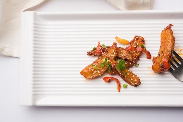 Honey chilli potato wedges, receita popular indiana-chinesa de entrada, guarnecida com gergelim e cebola. foco seletivo