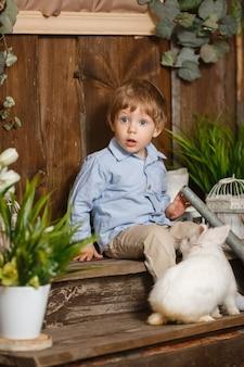 Honny criança brincando com o coelhinho da páscoa em uma grama verde. decoração rústica. estúdio, tiro em um fundo de madeira