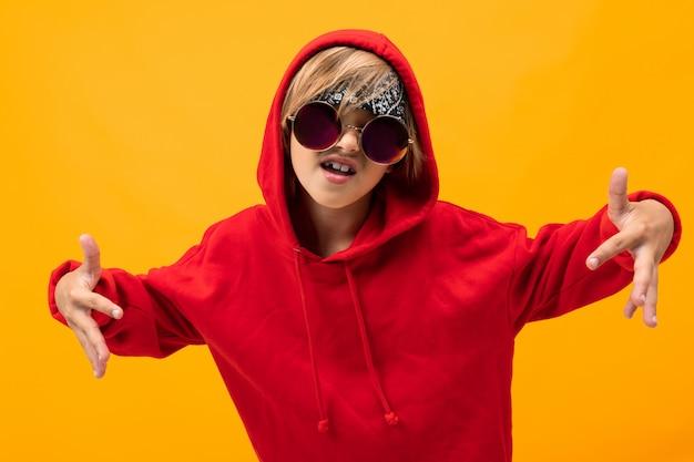 Hooligan criança dançando sobre um fundo amarelo, retrato emocional