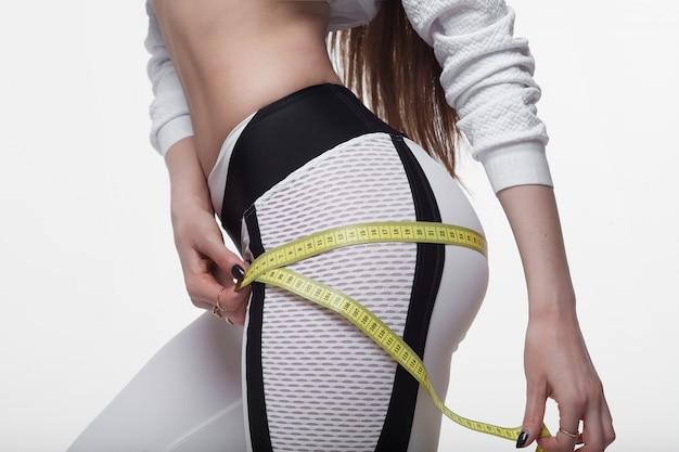 Hora da dieta para emagrecer. mulher de fitness cabe garota no sportswear com fita métrica, medindo a coxa em branco