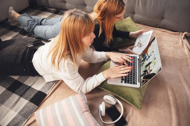 Hora da educação. jovens amigas, mulheres que usam gadgets para assistir cinema, fotos, cursos online, tirar selfie ou vlog, fazer compras. duas garotas caucasianas em casa usando laptop, tablet, smartphone, fones de ouvido.