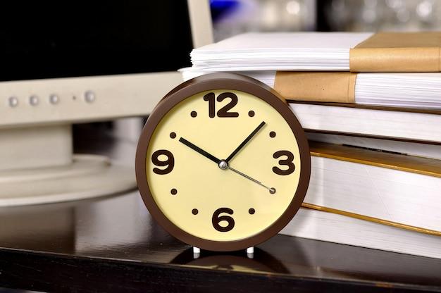 Hora da escola. relógio despertador e pilha de livros. conceito de educação.