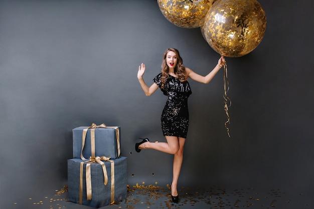 Hora da festa brilhante jovem linda em um vestido preto de luxo, de salto alto, com cabelo castanho longo e encaracolado segurando grandes balões cheios de enfeites dourados. presentes, festa de aniversário.
