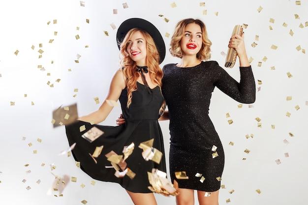 Hora da festa de duas melhores amigas, mulheres loiras em um vestido elegante coquetel preto posando no estúdio