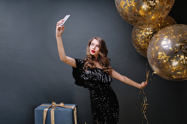 Hora da festa de uma jovem mulher atraente em um vestido preto de luxo, com cabelos longos e encaracolados morena fazendo selfie com grandes balões cheios de enfeites dourados. presentes, celebrando, modernos.