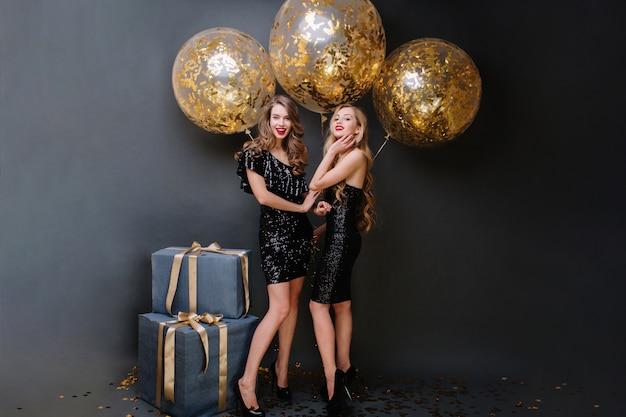 Hora da festa feliz de duas encantadoras jovens em vestidos pretos de luxo. cabelo comprido e cacheado, look atraente, presentes, grandes balões com enfeites dourados, sorrindo, se divertindo.