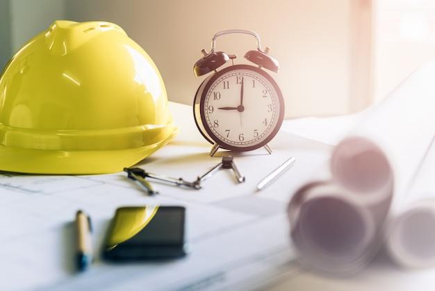Hora da manhã, já são nove horas. um relógio retrô que mostra as 9 horas da manhã na mesa do engenheiro projetista e arquiteto em um escritório com equipamento e papel de desenho para o plano de trabalho.
